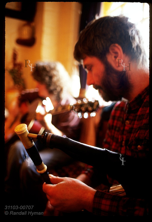 Musician plays the uilleann pipes (Irish bagpipes) during a pub session at Barr Na Sraide in town of Dingle, Ireland.