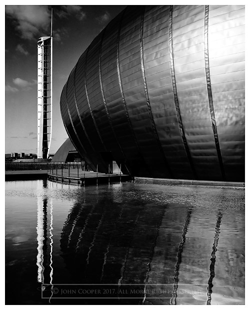 Black and white photograph of the Imax cinema at Glasgow Science Centre. Mounted print available to purchase.
