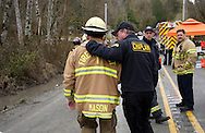 Snohomish County Fire Chief Steve Mason (L) talks with a chaplain near the mudslide near Oso, Washington as efforts continued to find victims March 26, 2014. The death toll from a massive landslide in Washington state stood at 24 on Wednesday, but the mud-stricken community braced for a higher body count as search teams combed through debris looking for scores of people still missing four days after the disaster.  REUTERS/Rick Wilking(UNITED STATES)
