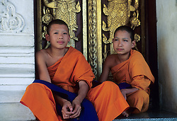 Asia, Thailand, Chiang Mai, boy monks in robes in dooway of Buddhist temple.