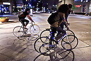 Three young men bicycle through a downtown intersection in Denver, Colorado. WATERMARKS WILL NOT APPEAR ON PRINTS OR LICENSED IMAGES.