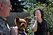 Alda Crill, right, fights to hold back her emotions while standing on the spot where her dog Belagrin was attacked by a pit bull as her husband Rikk Crill, holding Zoar, a 10 year old Yorkie, looks on Thursday, April 26, 2012 in their neighborhood..(Matthew Jonas/Times-Call)