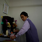 Grandmother Abe, a Togura resident who become a widower when her husband died during the 2011s tsunami that struck over the coastal areas of Japan, prays at the shrine in memory of her husband in the family's pre-fabricated house.
