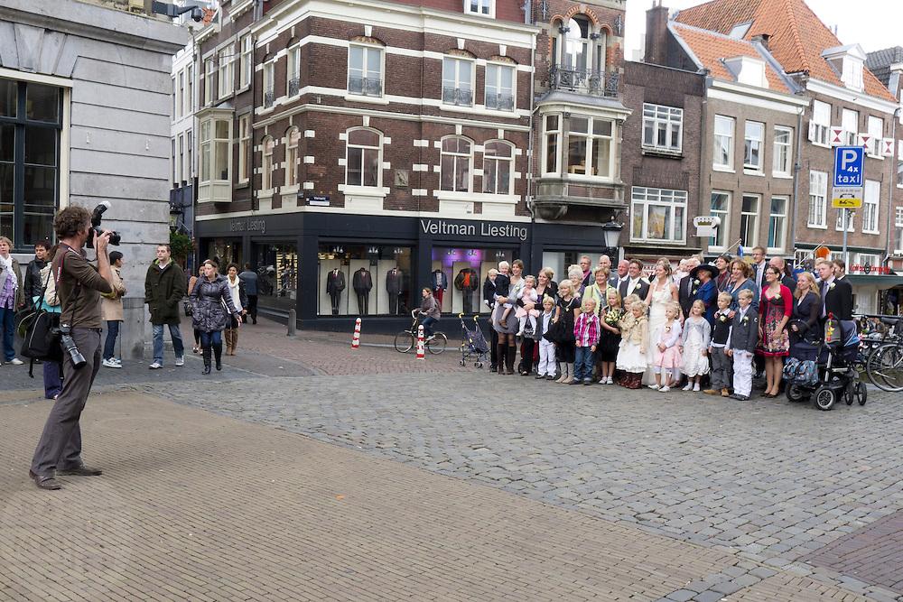 Een fotograaf maakt een groepsfoto van een bruidspaar met gezelschap in het centrum van Utrecht.<br /> <br /> A photographer is making a group portrait during a wedding at the center of Utrecht.