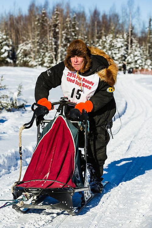 Musher Jack Berry competing in the Fur Rendezvous World Sled Dog Championships at Campbell Airstrip in Anchorage in Southcentral Alaska. Winter. Afternoon.