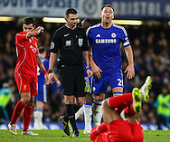 John Terry of Chelsea (rear-right) is about to be booked for a challenge on Raheem Sterling of Liverpool (front) during the Capital One Cup Semi Final 2nd Leg match between Chelsea and Liverpool at Stamford Bridge, London, England on 27 January 2015. Photo by David Horn.
