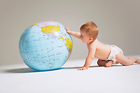 Baby touching inflatable globe