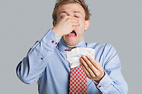 Front view of young man sneezing over colored background