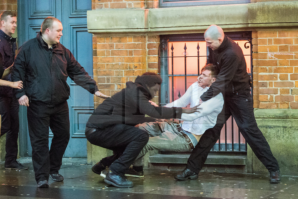 © Licensed to London News Pictures . 01/01/2015 . Manchester , UK . Bouncers carry a man away from Victoria's Lap Dancing Bar on Dantzic Street . Revellers usher in the New Year on a night out in Manchester City Centre .  Photo credit : Joel Goodman/LNP