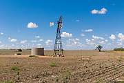 Windmill and water tank in dry cropping farm paddock under cumulus clouds in Clermont, Queensland, Australia.