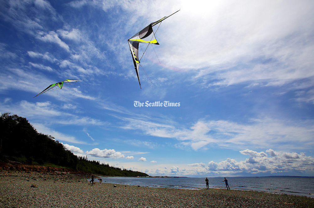 A man and his son played with stunt kites on the beach south of the Edmonds Marina as storm clouds began to appear on the horizon. (Mark Harrison / The Seattle Times)