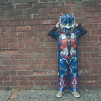 A young boy in a robot outfit standing beside a wall