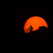 Andrew Whiteford wheelies under and through the light of sunset.