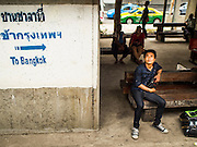 19 MARCH 2015 - BANGKOK, THAILAND:   A man sits in the station at Bang Khen, in the Bangkok suburbs, as a third class train on the Ayutthaya to Bangkok route passes him. The State Railways of Thailand (SRT), established in 1890, operates 4,043 kilometers of meter gauge track that reaches most parts of Thailand. Much of the track and many of the trains are poorly maintained and trains frequently run late. Accidents and mishaps are also commonplace. Successive governments, including the current military government, have promised to upgrade rail services. The military government has signed contracts with China to upgrade rail lines and bring high speed rail to Thailand. Japan has also expressed an interest in working on the Thai train system. Third class train travel is very inexpensive. Many lines are free for Thai citizens and even lines that aren't free are only a few Baht. Many third class tickets are under the equivalent of a dollar. Third class cars are not air-conditioned.      PHOTO BY JACK KURTZ
