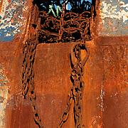 Rusted chains hanging from the side of an old fishing boat, Gloucester, MA