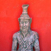 Thai religious hermit statue against a red temple background