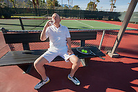 Senior male tennis player drinking water while relaxing on court