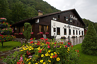 Exterior view of Chalet hotel and restaurant, located in Western Ukraine. Daylight view, with reflections in the wet ground after the rain.