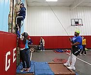 Chris Dougherty (from left) of Cedar Rapids is assisted on the climbing wall by Jocelen Gudgeon, Speech Therapist at University of Iowa Hospitals and Clinics, Katie Kass, Physical Therapist Assistant at St Luke's Hospital, and Uriel Moorer, Program Specialist at Camp Courageous during the Retreat & Refresh Stroke Camp at Camp Courageous in Monticello on Saturday, April 20, 2013. Dougherty had a stroke six years ago.