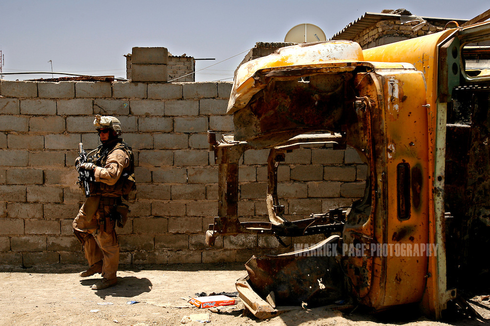 IRAQ, BASRA - JULY 5: SSgt. Patrick Hopwood (34) (R) of 1st Battalion 26th Brigade 2nd Division, from Miami, Florida walks past a burnout school bus, while conducting a joint patrol with Iraqi soldiers in the poverty stricken neighborhood of Hayaniyah, July 5, 2008 in Basra, Iraq. When British forces withdrew in 2007, Basra deteriorated into street battles between numerous Shiite militias and criminal gangs. In April 2008, Iraqi prime minister, Nouri al Maliki, sent two Iraqi army divisions to retake control of Basra. While the fighting has ended, unemployment is rife, at about 70 per cent. Since early 2008, Iraq's security situation has improved with oil production increasing, record government surplus and easing sectarian tensions. (Photo by Warrick Page)