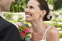 Mid adult bride and groom in garden smiling close-up