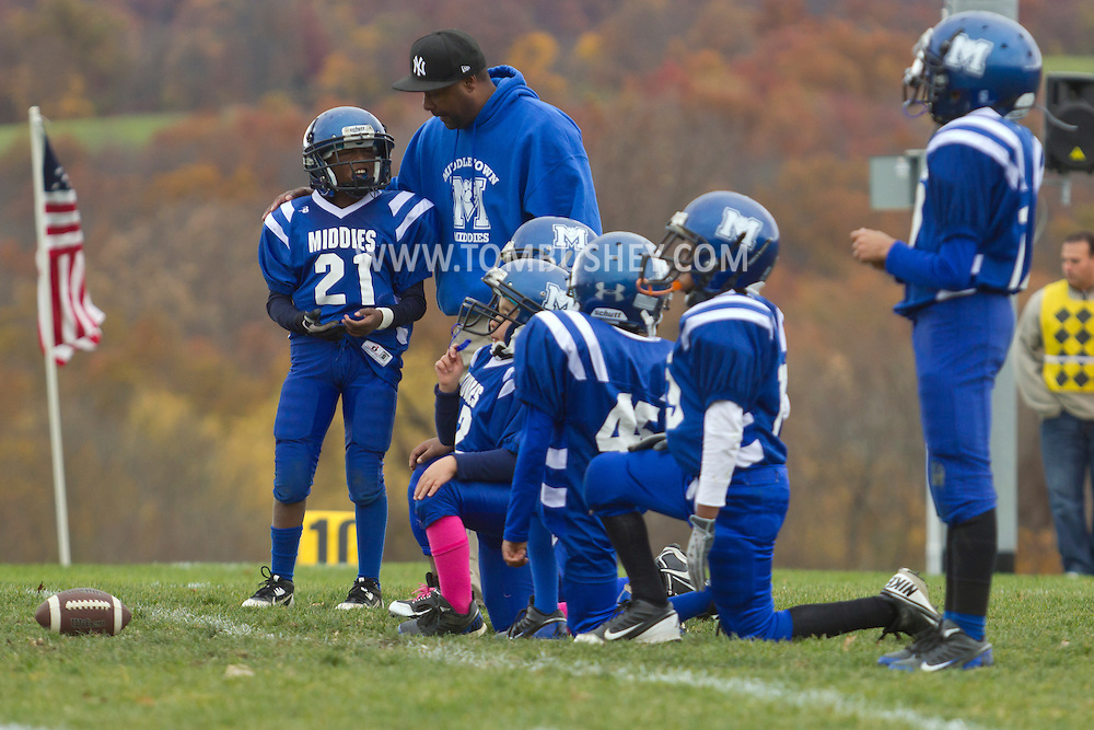 Salisbury Mills, New York  - A Middletown coach talks to his team in a huddle during an Orange County Youth Football League Division I playoff game at Lasser Field on Sunday, Nov. 3, 2013.