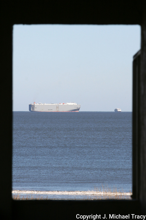 A cargo ship and a gambling boat on the horizon as viewed from an upstairs hallway.