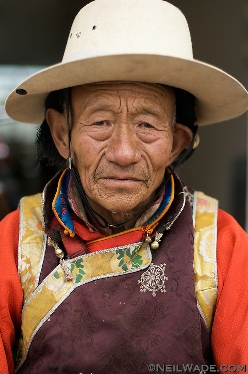 An elderly Tibetan man dressed in clothes specific to his tribe in Yushu, Tibet.