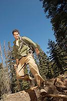 Hiker walking over log in forest