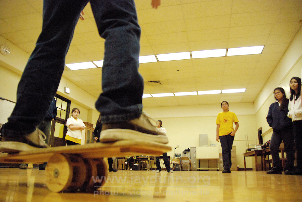 """USA, Chicago, IL, December 12, 2009.  Instructor Douglas Grew demonstrates the balance board. Students in the """"At-Risk After School Program"""" at Maria Saucedo Scholastic Academy receive training in basic physics principles through an innovative new program called """"Circus Galactica"""" put on by Pros Arts, a non-profit organization founded in 1978 by professional artists dedicated to the Pilsen/Little Village communities. In a residency that directly integrates science and art, veteran circus performers Douglas Grew and Paul Lopez bring the importance of """"balance, focus and presentation"""" into hands-on lessons about gravity, inertia, and the dynamics of objects in motion. Photo for Hoy by Jay Dunn."""