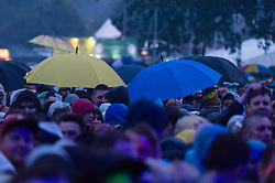 © Licensed to London News Pictures. 12/06/2015. Newport, UK.  Festival goers beneath torrential rail watch The Black Keys performing live at Isle of Wight Festival 2015, Day 2 Friday.  This afternoon and evening has seen torrential downpours of rain after the last day of hot sunshine.   Photo credit : Richard Isaac/LNP
