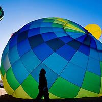 120112       Cable Hoover<br /> <br /> A crew member strolls past an inflating balloon during the Red Rock Balloon Rally at Red Rock Park Saturday.