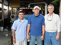 Portrait of owner with employees in car wash.
