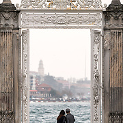A couple stands under one of the ornately decorated gates at Dolmabahçe Palace looking out over the Bosphorus Strait toward the Asian coast. Dolmabahçe Palace, on the banks of the Bosphorus Strait, was the administrative center of the Ottoman Empire from 1856 to 1887 and 1909 to 1922. Built and decorated in the Ottoman Baroque style, it stretches along a section of the European coast of the Bosphorus Strait in central Istanbul.