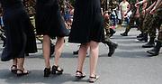Nederlandse militairen lopen op de laatste dag van de Nijmeegse Vierdaagse over de Via Gladiola, zoals de Sint Annastraat is omgedoopt tijdens het wandelevenement, langs vrouwen in rokken