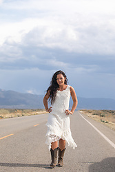 girl in a country dress and cowboy boots walking on a road