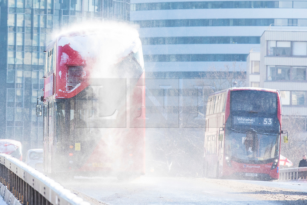 © Licensed to London News Pictures. 28/02/2018. London, UK. Snow is blown off the roof of a bus as it crosses Westminster Bridge. London saw heavy overnight snowfall as the 'Beast from the East brings freezing Siberian air to the UK. Photo credit: Rob Pinney/LNP