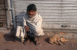 Man sitting by side of road with puppy asleep beside him; Punjab; India,