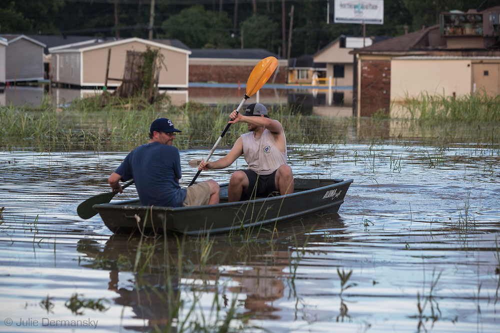 Aug, 15,, Brandon DeBate and Forrest Bellue use a boat to get to DeBate's home in Denham Springs.