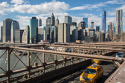 Two New York yellow taxicabs drive across the iconic Brooklyn Bridge away from Lower Manhattan, New York City, United States of America.  The sky scrapers of the financial district called Downtown Manhattan, can be seen in the background.  (photo by Andrew Aitchison / In pictures via Getty Images)