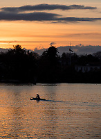 Paddlers race towards the sunset in the Inner Harbour of Victoria, BC.