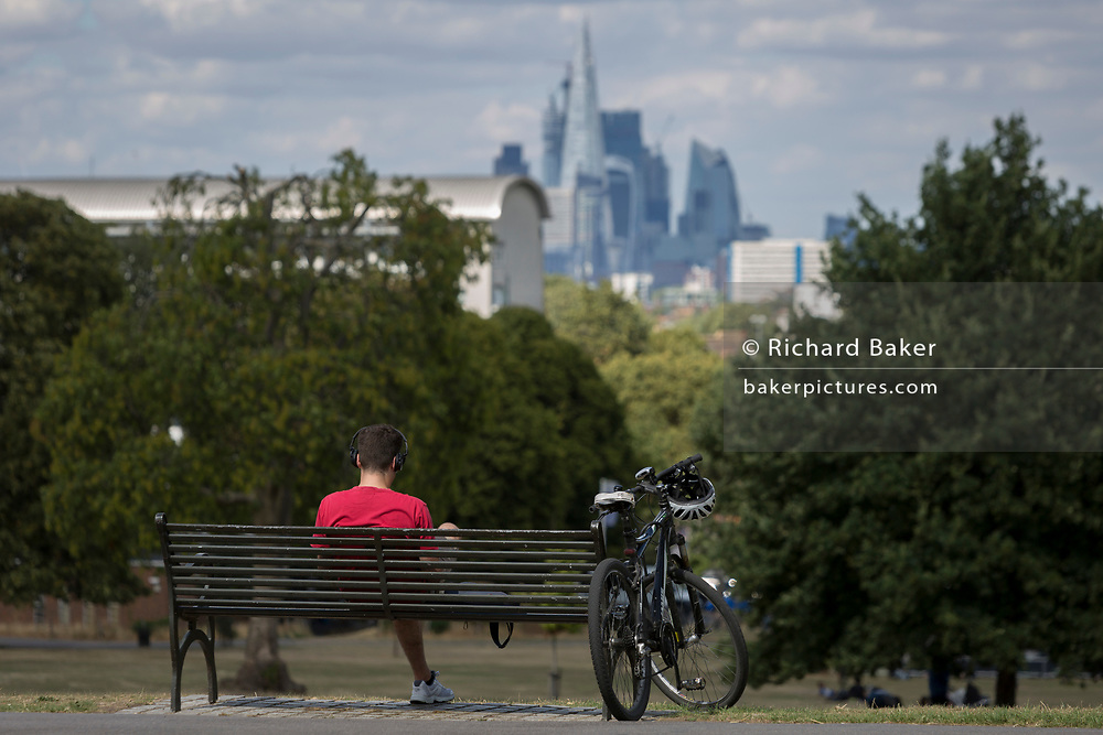 A cyclist wearing a red t-shirt sits on a park bench with the City of London's financial skyline in the distance, in Brockwell Park, on 8th August 2018, in London, England.