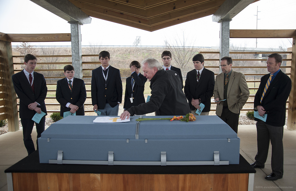 Buddy Dumeyera, the Louisville deputy coroner who runs the indigent burial program, places a flag on 48-year-old Francisco Carmona's casket as students from the St. Joseph of Arimathea Society at Trinity High School prepare to perform their duties Wednesday, Feb. 6, 2013 at Meadow View Cemetery in Louisville, Ky. The students are, from left, Paul Adams, 18, senior, Jeremy Gaines, 16, junior, Nolan Riley, 14, freshman, Greg Atchison, 17, senior, Sean Dageforde, 17, Jake Eddy, 18, senior, school principal Dan Zoeller and social studies teacher Chad Waggoner. (AP Photo/Brian Bohannon)