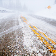 A winter storm blows snow accross the highway at the top of Teton Pass.
