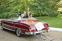 Mid adult bride and groom in vintage car waving hands