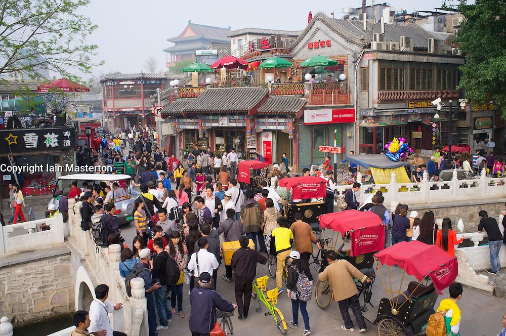 Busy street on historic bridge beside popular tourist location at Houhai Lake in Beijing China