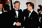 U.S. President Bill Clinton, center, shakes hands with Defense Secretary William Cohen in the receiving line during the State Dinner at the White House February 5, 1998 in Washington, DC.