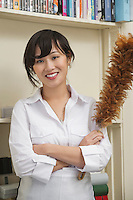 Portrait of female housekeeper holding feather duster
