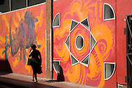 Woman walking past colorful mural in Capetown, South Africa.
