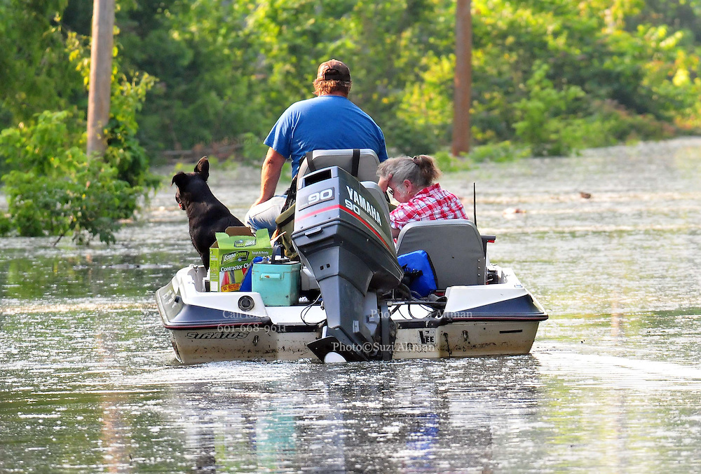 """8/11/11} Vicksburg} -- Vicksburg, MS, U.S.A. -- Patricia Clark hangs her head in despair as her boyfriend Mark Bridges,56, thrift store owner, and his dog """"baby girl""""  cruis down Cghicksaw Rd in his bassboat for her first look at her cabin. Mark Bridges and his girlfriend of 12 years Patricia Clark, a homeDepot garden employee, cruise down Chicksaw Rd in a bass boat in North Kings Community in Vicksburg Mississippi Wed. May 5th 2011. This is the firs time for Patricia to try and remove things from her trailer, that is built on 9ft stilts  AND THE WATER IS CURRENTLY AT 15 ft. and rising and is less than 12 inches from being flooded. Mark and Patricia have lived their all their lives and will return when the Mississippi River recedes,. ark has been helping his neighbors get their belongings to safety. Vicksburg a riverfront town steeped in war and sacrifice, gets set to battle an age-old companion: the Mississippi River. The city that fell to Ulysses S. Grant and the Union Army after a painful siege in 1863 is marshalling a modern flood-control arsenal to keep the swollen Mississippi from overwhelming its defenses. PHOTO©SUZIALTMAN.COM.Photo by Suzi Altman, Freelance."""